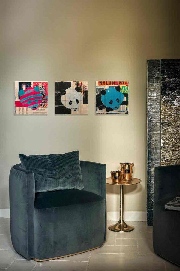 London Streetart Graffiti. Es zeigt das Bild eines Triptychons bestehend aus drei Panda Köpfen im Quadrat in den Farben Schwarz, Cyan und Pink, die an einer stylische eingerichteten Wohnzimmerwand hängen. Der Hintergrund auf dem die Panda Köpfe platziert sind, besteht aus verschiedenen Ausschnitten Londoner Zeitungen.