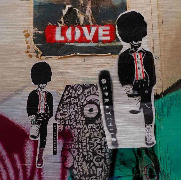"""London Streetart Graffiti. Es zeigt im unteren Bildteil das Bild von zwei britischen Guards mit Bärenfellmützen, die auf einem Bein stehen und sich mit dem anderen Bein, welches nach hinten geknickt ist, an einer Wand abstützen. Die Guards sind in den Farben Schwarz und Weiß, das Hemd welches sie tragen hat 2 Rote Streifen. Der Hintergrund ist zum Teil mit einem Schwarz-Weißen Muster sowie in den Farben Aubergine und Grün. Im oberen Bildteil ist die Fotografie einer Explosion mit der Aufschrift """"LOVE"""", welche mit weißen Buchstaben auf einen Roten Hintergrund ist."""