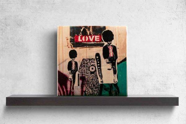 """London Streetart Graffiti. Es zeigt im unteren Bildteil das Bild von zwei britischen Guards mit Bärenfellmützen, die auf einem Bein stehen und sich mit dem anderen Bein, welches nach hinten geknickt ist, an einer Wand abstützen. Die Guards sind in den Farben Schwarz und Weiß, das Hemd welches sie tragen hat 2 Rote Streifen. Der Hintergrund ist zum Teil mit einem Schwarz-Weißen Muster sowie in den Farben Aubergine und Grün. Im oberen Bildteil ist die Fotografie einer Explosion mit der Aufschrift """"LOVE"""", welche mit weißen Buchstaben auf einen Roten Hintergrund ist. Das Bild steht auf einem schwarzen Wandregal vor weißem Hintergrund."""