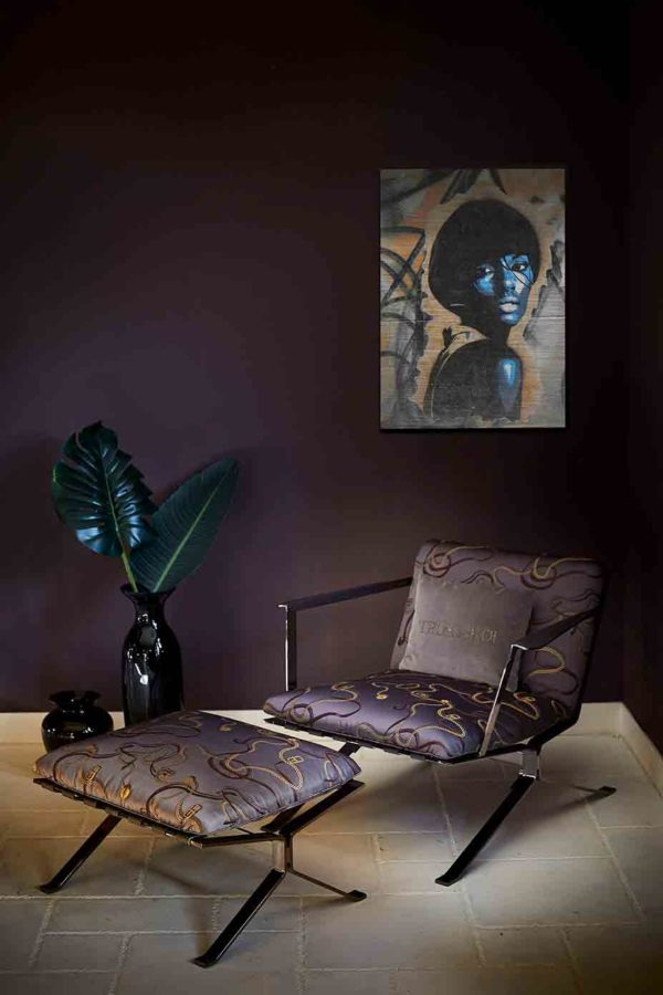 London Graffiti. Es zeigt das Bild einer afroamerikanischen Frau im Stil der 70's die lasziv über die Schulter blickt, die an einer stylische eingerichteten Wohnzimmerwand hängen. Sie trägt einen Pagenkopf mit Pony, plakativ reduziert dargestellt in Blau- und Weißtönen. Der Hintergrund ist eine Graffiti Wand in komplementären Orangetönen und schwarzen Tags.