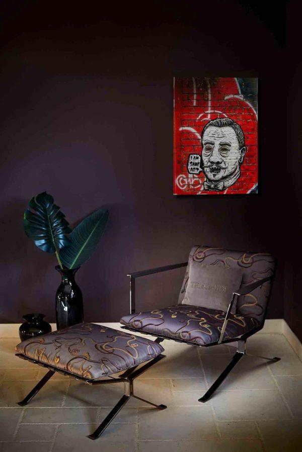 """London Streetart Graffiti. Es zeigt das Bild von einem Männerkopf in Strichzeichnung mit den Farben Schwarz-Weiß. Abweichend ist die Umrandung seiner Augen in einem dunklen Gelbton. Die Frisur des Mannes und der geschwungene Oberlippenbart sind im Stil der 1920er Jahre. Der Mund ist offen und neben dem Gesicht ist eine Sprechblase mit dem Satz """"I'AM SOME ART"""". Am Hals trägt er eine Fliege. Der Hintergrund des Bildes ist eine Rot gestrichene Backsteinmauer mit Weißen Graffiti Streifen. Mauerteile an der rechten Seite des Bildes sind Schwarz. Das Bild hängt an einer stylische eingerichteten Wohnzimmerwand."""