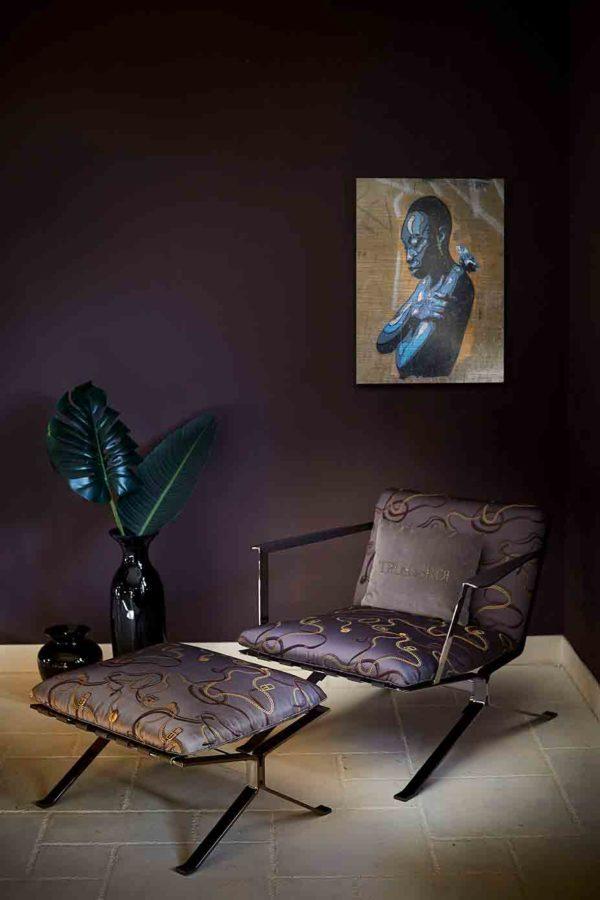 London Streetart Graffiti. Es zeigt das Bild einer Frau mit sehr kurzen Haaren, die nach unten blickt und ihre Arme um den eigenen Körper schlingt. Auf Ihrer Schulter sitzt ein kleiner Vogel. Das Gesicht der Frau und ihre Körpervorderseite, sowie der kleine Vogel ist in verschiedenen Blautönen sowie Weiß und Schwarz. Die Haare und die Körperrückseite sind Schwarz. Im Hintergrund ist eine Wand in Beigetönen und einige Graffiti Streifen in Weiß und Grau. Das Bild hängt an einer stylische eingerichteten Wohnzimmerwand.