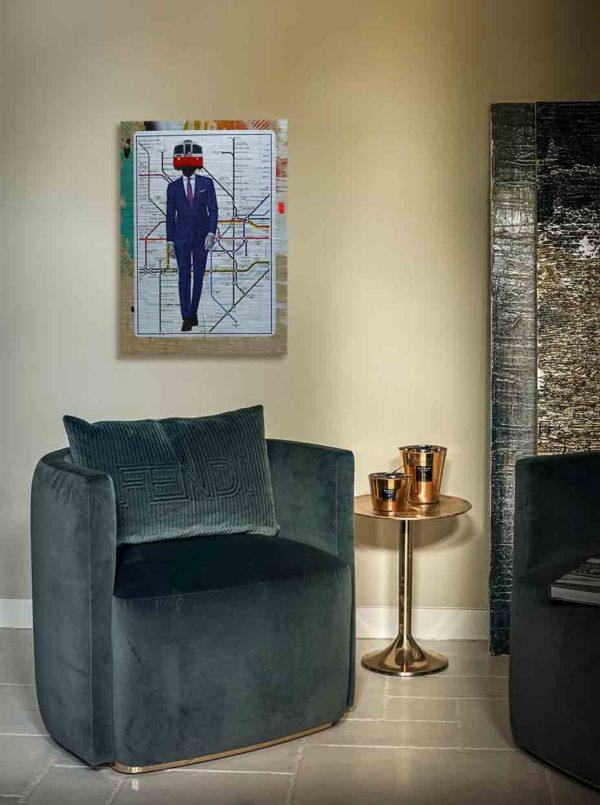 London Streetart Graffiti. Das Bild zeigt eine Londoner U-Bahn-Karte auf der ein Mann mit einem dunkelblauen Anzug abgebildet ist. Der Mann trägt ein weißes Hemd und eine Krawatte. Auf dem Hals des Mannes ist anstatt seines Kopfes, die Front eines U-Bahn Zuges abgebildet. Die U-Bahn hat die Farben Rot und Weiß. Um die U-Bahn-Karte ist noch ein Rand in den verschiedenen Beigetönen, Gelb, Orange und Türkis. Das Bild hängt an einer stylische eingerichteten Wohnzimmerwand.