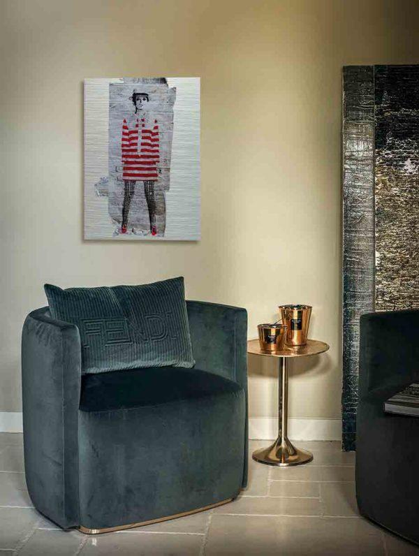 """London Streetart Graffiti. Es zeigt das Bild einer Frau mit einem Rot-Weiß gestreiften kurzen Kleid und einer Schwarz-Weiß karierten Strumpfhose Die Frau ist schlank und trägt einen Hut, sie könnte die Person """"Twiggy"""" darstellen. Der Hintergrund ist eine Weiße Backsteinwand. Das Bild hängt an einer stylische eingerichteten Wohnzimmerwand."""