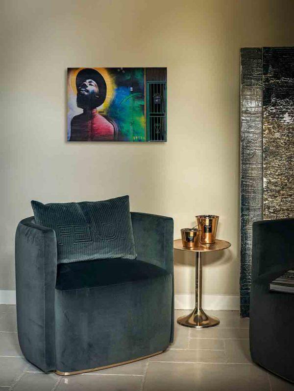 London Streetart Graffiti. Es zeigt das Bild eines Mannes, der einen Hut und einen Vollbart trägt. Er neigt den Kopf nach hinten und hält die Augen geschlossen. Die Kleidung des Mannes ist in verschiedenen Rottönen. Um den Kopf des Mannes ist der Hintergrund in verschiedenen Gelbtönen. Auf der rechten Bildseite ist die Wand in Blau, Grün und Schwarz. Am rechten Rand ist eine grüne Tür mit einem Briefkasten. Das Bild hängt an einer stylische eingerichteten Wohnzimmerwand.
