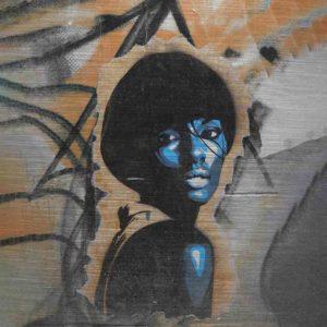 London Graffiti. Es zeigt das Bild einer afroamerikanischen Frau im Stil der 70's die lasziv über die Schulter blickt. Sie trägt einen Pagenkopf mit Pony, plakativ reduziert dargestellt in Blau- und Weißtönen. Der Hintergrund ist eine Graffiti Wand in komplementären Orangetönen und schwarzen Tags.