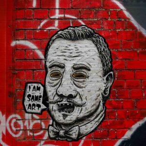 """London Streetart Graffiti. Es zeigt das Bild von einem Männerkopf in Strichzeichnung mit den Farben Schwarz-Weiß. Abweichend ist die Umrandung seiner Augen in einem dunklen Gelbton. Die Frisur des Mannes und der geschwungene Oberlippenbart sind im Stil der 1920er Jahre. Der Mund ist offen und neben dem Gesicht ist eine Sprechblase mit dem Satz """"I'AM SOME ART"""". Am Hals trägt er eine Fliege. Der Hintergrund des Bildes ist eine Rot gestrichene Backsteinmauer mit Weißen Graffiti Streifen. Mauerteile an der rechten Seite des Bildes sind Schwarz."""