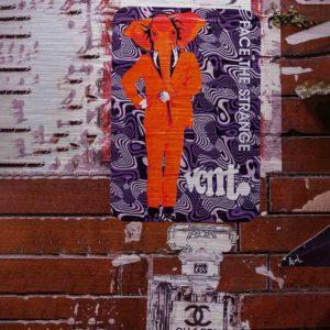 London Streetart Graffiti. Es zeigt das Bild einer braunen Backsteinwand, die mit einem Plakat beklebt ist. Auf diesem Plakat ist ein Menschenkörper mit einem Elefantenkopf abgebildet ist. Der Chimäre hat die Farbe Orange und ist bekleidet mit einem Herrenanzug ebenfalls in Orange. Der Hintergrund des Plakates ist mit Lila-Weißen Wellen aufgefüllt. Am unteren Bildrand ist der obere Teil einer Parfumflasche abgebildet.