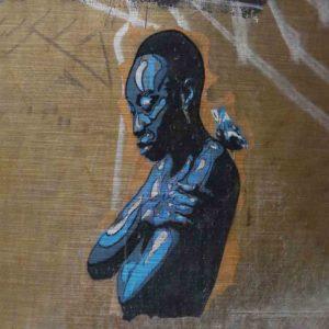 London Streetart Graffiti. Es zeigt das Bild einer Frau mit sehr kurzen Haaren, die nach unten blickt und ihre Arme um den eigenen Körper schlingt. Auf Ihrer Schulter sitzt ein kleiner Vogel. Das Gesicht der Frau und ihre Körpervorderseite, sowie der kleine Vogel ist in verschiedenen Blautönen sowie Weiß und Schwarz. Die Haare und die Körperrückseite sind Schwarz. Im Hintergrund ist eine Wand in Beigetönen und einige Graffiti Streifen in Weiß und Grau.