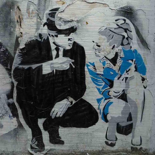 London Streetart Graffiti. Es zeigt das Bild eines Mannes und einer Frau, welche in der Hocke kniend miteinander sprechen. Der Mann trägt einen schwarzen Anzug und einen Hut und hält in seiner rechten Hand eine Zigarette. Die Frau trägt ein kurzes schickes blaues Kleid und hat eine Hochfrisur im Stil der 70'er Jahre. Im Hintergrund ist eine Graffiti Wand in den Farben, Schwarz-Weiß und Grau.