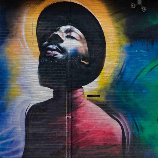 London Streetart Graffiti. Es zeigt das Bild eines Mannes, der einen Hut und einen Vollbart trägt. Er neigt den Kopf nach hinten und hält die Augen geschlossen. Die Kleidung des Mannes ist in verschiedenen Rottönen. Um den Kopf des Mannes ist der Hintergrund in verschiedenen Gelbtönen. Auf der rechten Bildseite ist die Wand in Blau, Grün und Schwarz. Am rechten Rand ist eine grüne Tür mit einem Briefkasten.