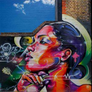 London Streetart Graffiti. Es zeigt das Bild der Seitenansicht einer Frau bis zum Hals. Das Graffiti Bild ist mit Sprühdosen auf eine Wand gesprüht. Die Frau blickt stolz nach vorne und Ihre Haare trägt sie streng nach hinten. Unter dem Kinn ist ihre Hand. Die Frau ist bunt, in den Farben Rot, Orange, Pink, Lila Blau, Schwarz, Gelb. Die Mauer nimmt nicht den ganzen Bildhintergrund ein, im linken oberen Teil ist ein strahlend blauer Himmel zu sehen. Außerdem sind auf der Wand noch viele Graffiti Elemente in den Farben Schwarz, Weiß, Grün und Gelb zu sehen.