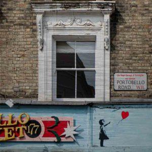 """London Streetart Graffiti. Es zeigt das Bild einer Hausfront mit 3 Fenstern. An der Backsteinwand ist ein Straßenschild mit der Straßenbezeichnung """"Portobello Road"""". Unter den Fenstern ist der Schriftzug eines Geschäftes mit dem Namen """"Portobello Market"""" und an der rechten Seite des Schildes ist die Figur eines Mädchens abgebildet, welches einen Luftballon in Herzform gerade losgelassen hat. Die Fenster sind Weiß, die Backsteinwand hellgrau und Schild des Geschäftes ist in den Farben, Hellblau, Rot, Rose, Schwarz und Gold."""