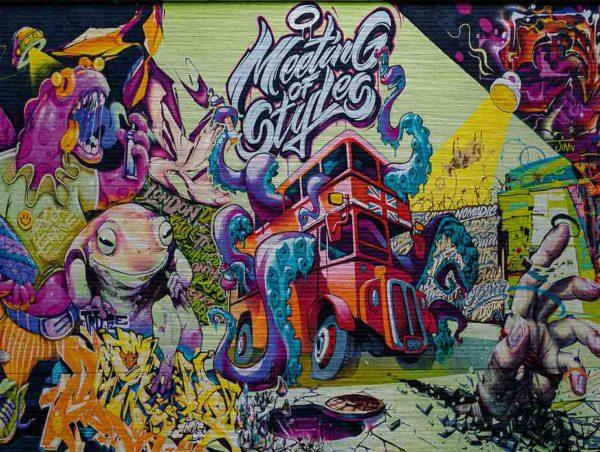"""London Streetart Graffiti. Es zeigt das Bild einer mit Graffiti besprühten Wand mit folgenden Motiven: London-Bus aus dem die Arme eines Oktopusses greifen, eine Hand welche eine Fläche des Bodens durchbrochen hat, der Schriftzug """"Meeting Of Styles"""", ein Frosch und andere Figuren und Gegenstände. Das gesamte Bild ist bunt."""