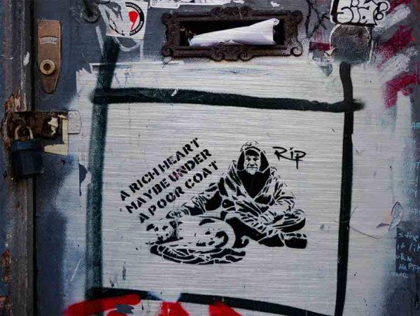 """London Streetart Graffiti. Es zeigt das Bild von einer Tür, auf der das Bild eines sitzenden älteren Mannes und eines liegenden Hundes zu sehen ist. Das Bild soll einen Obdachlosen mit seinem Hund darstellen. Links ist schräg der Text """"A RICH HEART MAYBE UNDER A POOR COAT"""" geschrieben. Die Figuren und der Text sind schwarz auf weißem Hintergrund. Das Bild des Obdachlosen ist mit einem schwarzen Streifen umrandet."""