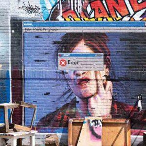 """London Streetart Graffiti. Es zeigt das provokante Bild eines Computerbildschirms auf dem eine Frau bis zur Schulter abgebildet ist, welche ihren Kopf auf einer Hand auflehnt und mit dem Mittelfinger noch oben zeigt. Über den Augen der Frau ist die EDV-Meldung """"ERROR"""". Im Hintergrund des Computerbildschirms ist eine bunte Graffitibacksteinwand. Im Vordergrund sind im unteren Bildteil verschiedene alte Möbelstücke. Das Bild ist bunt."""