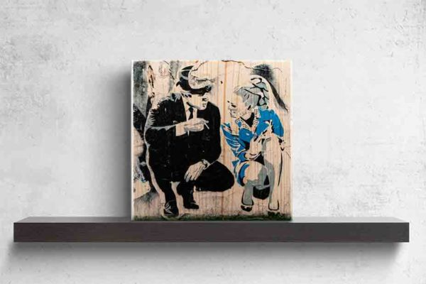London Streetart Graffiti. Es zeigt das Bild eines Mannes und einer Frau, welche in der Hocke kniend miteinander sprechen. Der Mann trägt einen schwarzen Anzug und einen Hut und hält in seiner rechten Hand eine Zigarette. Die Frau trägt ein kurzes schickes blaues Kleid und hat eine Hochfrisur im Stil der 70'er Jahre. Im Hintergrund ist eine Graffiti Wand in den Farben, Schwarz-Weiß und Grau. Das Bild steht auf einem schwarzen Wandregal vor weißem Hintergrund.