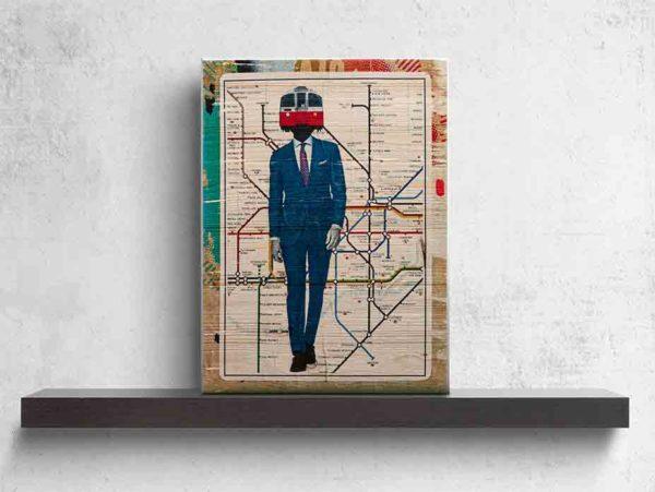 London Streetart Graffiti. Das Bild zeigt eine Londoner U-Bahn-Karte auf der ein Mann mit einem dunkelblauen Anzug abgebildet ist. Der Mann trägt ein weißes Hemd und eine Krawatte. Auf dem Hals des Mannes ist anstatt seines Kopfes, die Front eines U-Bahn Zuges abgebildet. Die U-Bahn hat die Farben Rot und Weiß. Um die U-Bahn-Karte ist noch ein Rand in den verschiedenen Beigetönen, Gelb, Orange und Türkis. Das Bild steht auf einem schwarzen Wandregal vor weißem Hintergrund.