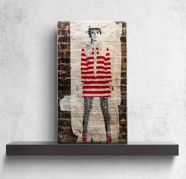 """London Streetart Graffiti. Es zeigt das Bild einer Frau mit einem Rot-Weiß gestreiften kurzen Kleid und einer Schwarz-Weiß karierten Strumpfhose Die Frau ist schlank und trägt einen Hut, sie könnte die Person """"Twiggy"""" darstellen. Der Hintergrund ist eine Weiße Backsteinwand. Das Bild steht auf einem schwarzen Wandregal vor weißem Hintergrund."""