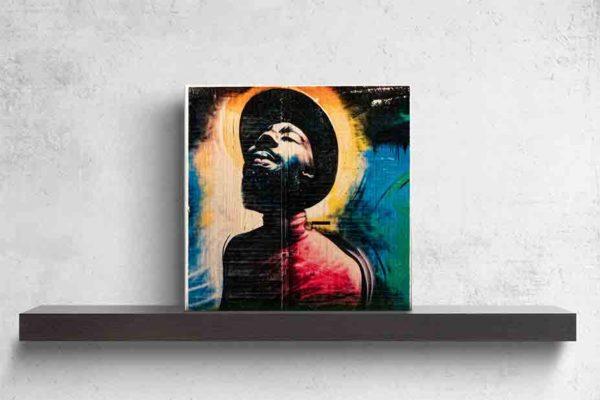 London Streetart Graffiti. Es zeigt das Bild eines Mannes, der einen Hut und einen Vollbart trägt. Er neigt den Kopf nach hinten und hält die Augen geschlossen. Die Kleidung des Mannes ist in verschiedenen Rottönen. Um den Kopf des Mannes ist der Hintergrund in verschiedenen Gelbtönen. Auf der rechten Bildseite ist die Wand in Blau, Grün und Schwarz. Am rechten Rand ist eine grüne Tür mit einem Briefkasten. Das Bild steht auf einem schwarzen Wandregal vor weißem Hintergrund.