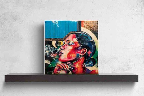 London Streetart Graffiti. Es zeigt das Bild der Seitenansicht einer Frau bis zum Hals. Das Graffiti Bild ist mit Sprühdosen auf eine Wand gesprüht. Die Frau blickt stolz nach vorne und Ihre Haare trägt sie streng nach hinten. Unter dem Kinn ist ihre Hand. Die Frau ist bunt, in den Farben Rot, Orange, Pink, Lila Blau, Schwarz, Gelb. Die Mauer nimmt nicht den ganzen Bildhintergrund ein, im linken oberen Teil ist ein strahlend blauer Himmel zu sehen. Außerdem sind auf der Wand noch viele Graffiti Elemente in den Farben Schwarz, Weiß, Grün und Gelb zu sehen. Das Bild steht auf einem schwarzen Wandregal vor weißem Hintergrund.