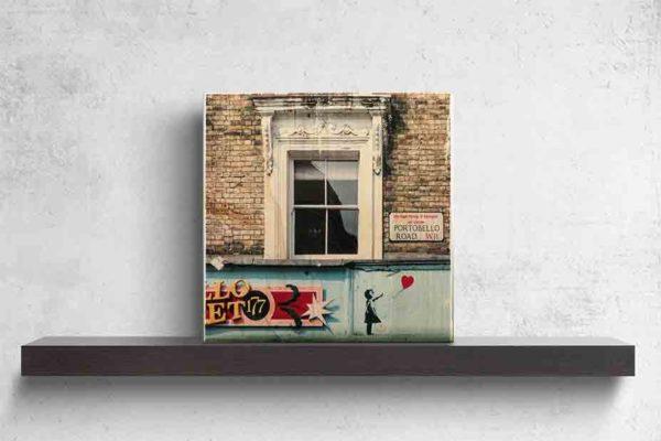 """London Streetart Graffiti. Es zeigt das Bild einer Hausfront mit 3 Fenstern. An der Backsteinwand ist ein Straßenschild mit der Straßenbezeichnung """"Portobello Road"""". Unter den Fenstern ist der Schriftzug eines Geschäftes mit dem Namen """"Portobello Market"""" und an der rechten Seite des Schildes ist die Figur eines Mädchens abgebildet, welches einen Luftballon in Herzform gerade losgelassen hat. Die Fenster sind Weiß, die Backsteinwand hellgrau und Schild des Geschäftes ist in den Farben, Hellblau, Rot, Rose, Schwarz und Gold. Das Bild steht auf einem schwarzen Wandregal vor weißem Hintergrund."""