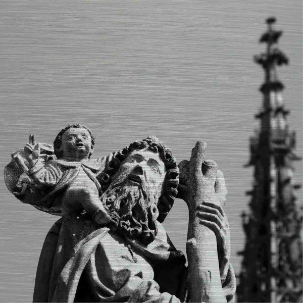 Ulmer Brunnenbild. Es zeigt das Bild des oberen Teils des Christopherus Brunnens in Ulm. Rechts im Bildteil die Spitze des Ulmer Münsters. Der Brunnen zeigt das Abbild eines Mannes mit einem langen Bart auf dessen Schulter eine kleiner Junge, der einen Engel darstellen soll, sitzt. Der Mann und der Engel sehen antik aus. Das Bild ist in den Farben Schwarz-Weiss.