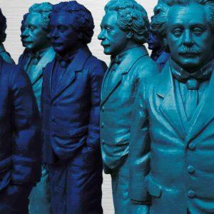 Einstein Figuren auf dem Ulmer Münsterplatz. Es zeigt das Bild von mehreren Skulpturen, die Albert Einstein darstellen sollen. Die Figuren sind in den Farben Dunkelblau und Türkis. Die Figuren sind stehend und tragen einen Herrenanzug. Die Figuren haben eine Hand ist in der Hosentasche und der andere Arm ist seitlich des Körpers.