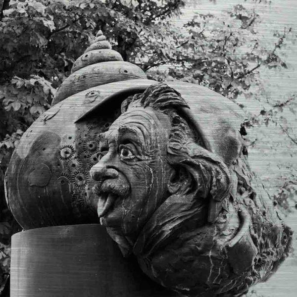 Ulmer Brunnenbild. Es zeigt das Bild einer Bronzeguss-Plastik von Albert Einstein. Die Seitenansicht seines Gesichts schaut mit herausgestreckter Zunge aus einem Schneckenhaus. Das Schneckenhaus wiederum liegt auf einem Raketenrumpf. Das Bild ist in den Farben Schwarz-Weiss.