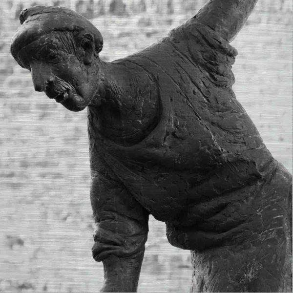 """Ulmer Brunnenbild. Es zeigt das Bild eines Mannes der ein antikes Aussehen hat. Einer seiner Arme zeigt nach unten und der andere nach oben. Er trägt eine altertümliche Kappe und soll die Figur des Griesbadsmichel's darstellen, welcher ein Knecht war und in dem Ulmer Altstadtviertel """"Auf dem Kreuz"""" lebte. Das Bild ist in den Farben Schwarz-Weiss."""