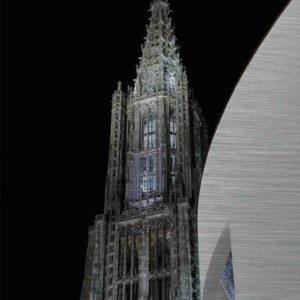 Ulmer Münster und Stadthaus Ulm. Es zeigt das Bild einer Nachtaufnahme des Ulmer Münsters mit seiner wunderschönen Lichtinstallation im Turm des Ulmer Münsters. Rechts im Bildteil ist das Ulmer Stadthaus, welches eine klare und moderne Architektur hat und komplett in Weiss ist. Entworfen wurde das Stadthaus vom New Yorker Architekten Richard Meier. Der Himmel im Hintergrund ist durchgehend schwarz.