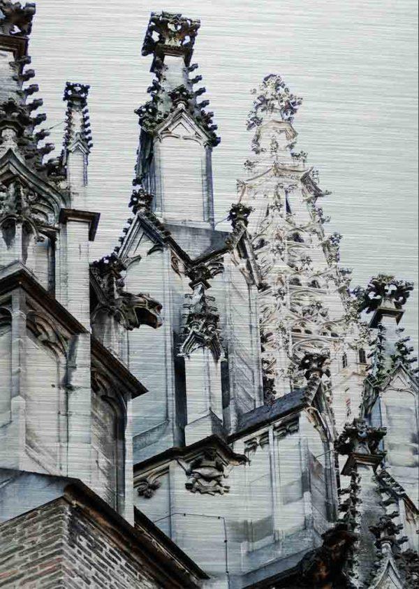 Ulmer Münster Seitenansicht. Es zeigt das Bild von verschiedenen Turmspitzen, eine davon ist die Spitze des Ulmer Münsters. Im linken Bildteil sind weitere kleine Turmspitzen, welche sich an den Seitenschiffen des Ulmer Münsters befinden. Das Bild ist hauptsächlich in den Farben Schwarz-Weiss.