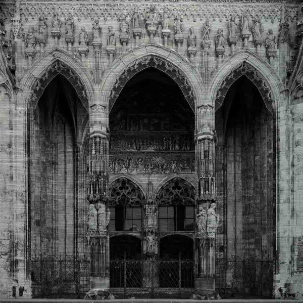Hauptportal des Ulmer Münsters. Es zeigt das Bild des Hauptportals des Ulmer Münsters mit zwei großen Holztüren und zwei schön verzierte Säulen vor den Holztüren. Im und um das Portal wird mit verschiedenen Figuren und Darstellungen die Erschaffung der Welt erzählt. Das Bild ist in den Farben Schwarz-Weiss.