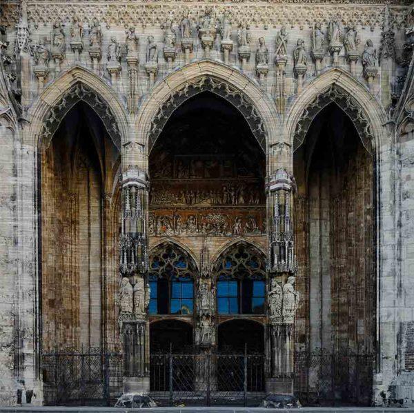 Hauptportal des Ulmer Münsters. Es zeigt das Bild des Hauptportals des Ulmer Münsters mit zwei großen Holztüren und zwei schön verzierte Säulen vor den Holztüren. Im und um das Portal wird mit verschiedenen Figuren und Darstellungen die Erschaffung der Welt erzählt. Das Bild ist farbig..