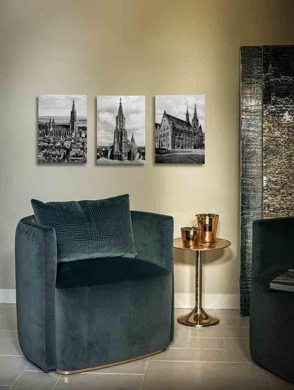 Beschreibung Beispielbild: Das Bild zeigt den Teilbereich eines modern eingerichteten Wohnraums mit dunkelgrünem Lounge-Sessel. Daneben befindet sich ein kupferfarbener Beistelltisch mit kupferfarbenen Wohnaccessoires, der Boden ist hell gefliest. An der beige gestrichenen Wand hinter dem Sessel hängt ein Triptychon aus historischen Fotografien der Stadt Ulm. Das linke Bild zeigt das Ulmer Münster mit Stadthäusern, das mittlere nur das Ulmer Münster, das rechte Bild das Ulmer Rathaus. Die drei Motive sind auf Alu Dibond, einen metallischen Untergrund, gedruckt und reflektieren diffus das Raumlicht.