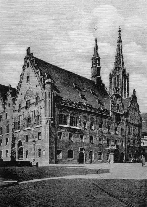 Ulmer Rathaus. Das Bild zeigt eine historische Aufnahme des Ulmer Rathauses im Vordergrund. Das Rathaus hat prächtigen Außenfresken, einer astronomischen Uhr und einen kleinen Turm. Im Hintergrund ist der obere Turmteil des Ulmer Münsters zu sehen. Vor dem Rathaus ist ein Platz mit einem Brunnen.