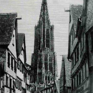 Ulmer Münster. Das Bild zeigt eine historische Aufnahme aus der Walfischgasse in Ulm mit Blick auf den Turm des Ulmer Münsters. Auf der Straße stehen Autos und an beiden Straßenseiten sind die Giebel der Stadthäuser zu sehen.