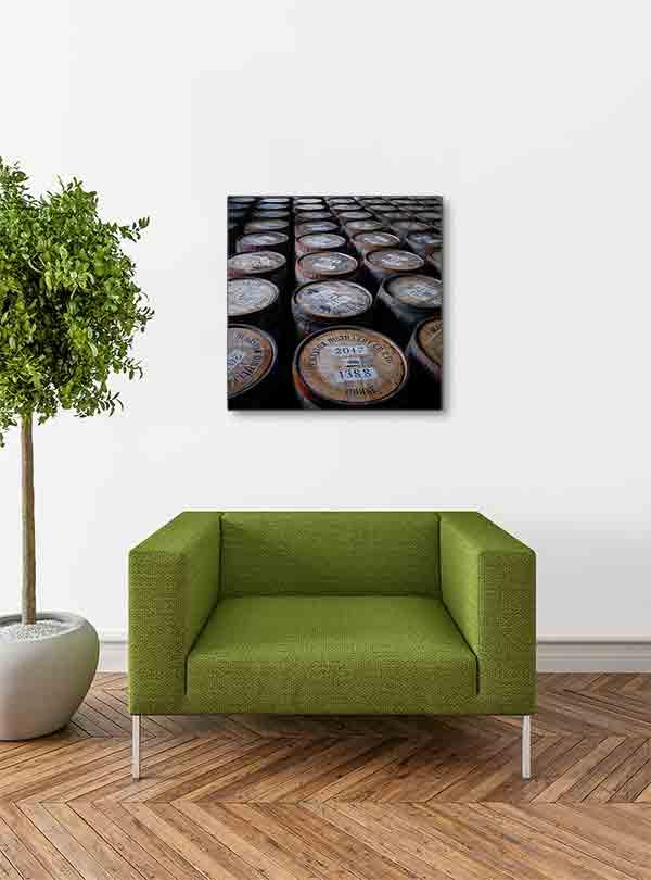 Schottland Brennerei Deanston Whiskyfässer. Es zeigt das Bild von Whiskyfässern in einer Destillerie in den schottischen Highlands. Die Holzfässer sind stehend mit dem Fassdeckel nach oben, so dass die Bezeichnung der Inhalte gut zu lesen ist. Das Bild ist quadratisch und in Farbe. Das Bild hängt an einer stylische eingerichteten Wohnzimmerwand.
