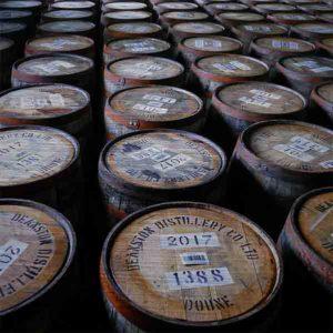 Schottland Brennerei Deanston Whiskyfässer. Es zeigt das Bild von Whiskyfässern in einer Destillerie in den schottischen Highlands. Die Holzfässer sind stehend mit dem Fassdeckel nach oben, so dass die Bezeichnung der Inhalte gut zu lesen ist. Das Bild ist quadratisch und in Farbe.