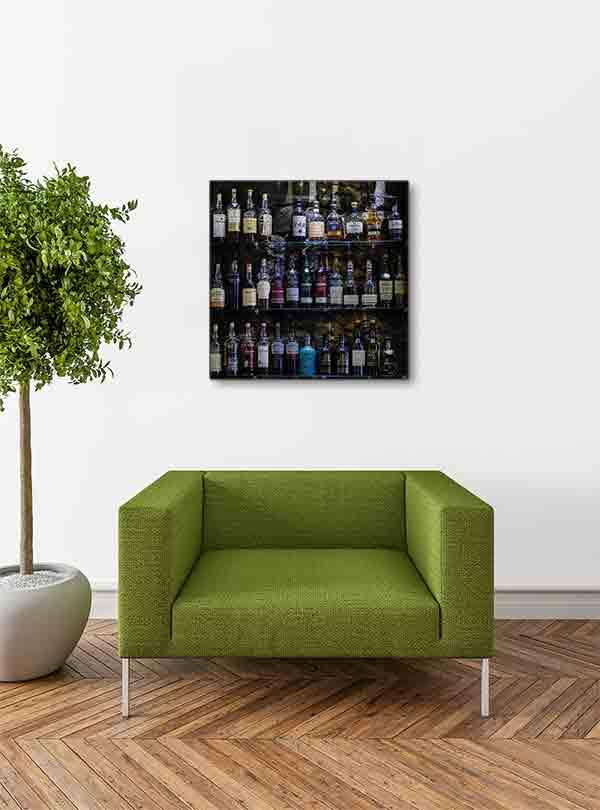 Edinburgh Bar Whiskyflaschen. Es zeigt das Bild von Whiskyflaschen, welche auf einem Regal vor einer dunklen Natursteinwand stehen. Es sind 3 Regalböden aus Glas, die alle gefüllt sind mit Whiskyflaschen vorrangig aus Schottland. Das Bild ist quadratisch und in Farbe. Das Bild hängt an einer stylische eingerichteten Wohnzimmerwand.