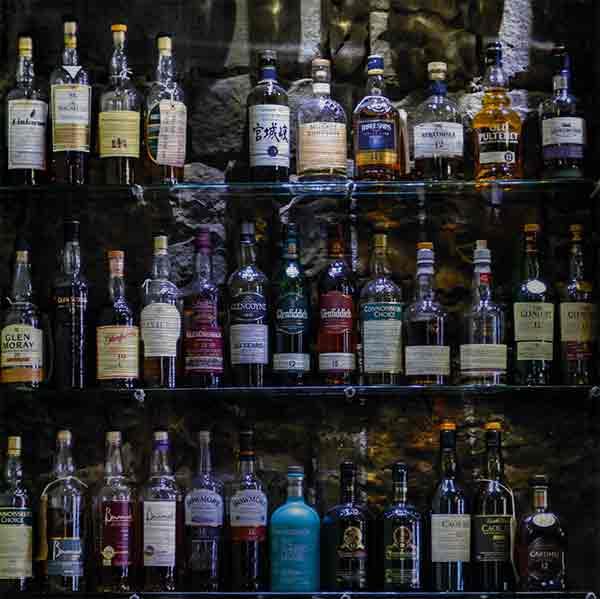 Edinburgh Bar Whiskyflaschen. Es zeigt das Bild von Whiskyflaschen, welche auf einem Regal vor einer dunklen Natursteinwand stehen. Es sind 3 Regalböden aus Glas, die alle gefüllt sind mit Whiskyflaschen vorrangig aus Schottland. Das Bild ist quadratisch und in Farbe.