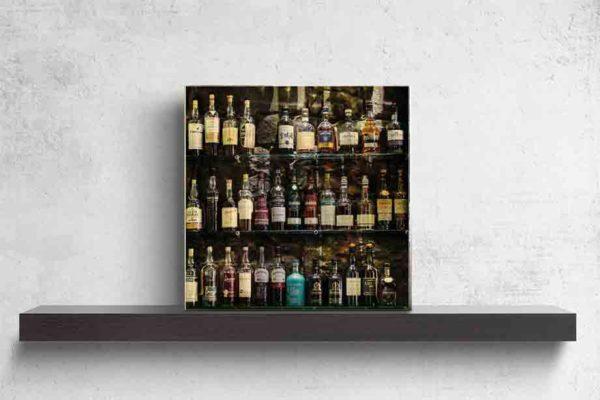 Edinburgh Bar Whiskyflaschen. Es zeigt das Bild von Whiskyflaschen, welche auf einem Regal vor einer dunklen Natursteinwand stehen. Es sind 3 Regalböden aus Glas, die alle gefüllt sind mit Whiskyflaschen vorrangig aus Schottland. Das Bild ist quadratisch und in Farbe. Das Bild steht auf einem schwarzen Wandregal vor weißem Hintergrund.