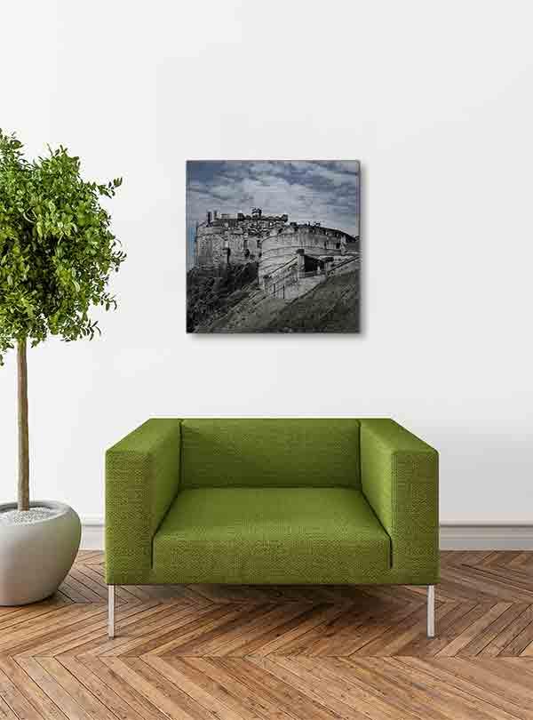 """Schottland Edinburgh. Es zeigt das Bild des Wahrzeichens der Stadt Edinburgh, die Höhenburg """"Edinburgh Castle"""", gelegen auf einem Felsen dem """"Castle Rock"""". Die Burg ist aus grauem Naturstein und es sind 2 Gebäude der Burg zu sehen. Ein Gebäude ist rund und das andere Gebäude ist eckig. Unter dem eckigen Gebäude ist der Felsen zu sehen auf dem die Burg gebaut ist. Außerdem ist eine Mauer zu sehen, hinter welcher sich der Vorhof zur Burg befindet. Das Alu Dibond Bild hängt an einer stylische eingerichteten Wohnzimmerwand."""