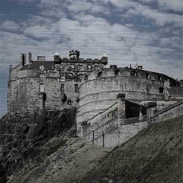 """Schottland Edinburgh. Es zeigt das Bild des Wahrzeichens der Stadt Edinburgh, die Höhenburg """"Edinburgh Castle"""", gelegen auf einem Felsen dem """"Castle Rock"""". Die Burg ist aus grauem Naturstein und es sind 2 Gebäude der Burg zu sehen. Ein Gebäude ist rund und das andere Gebäude ist eckig. Unter dem eckigen Gebäude ist der Felsen zu sehen auf dem die Burg gebaut ist. Außerdem ist eine Mauer zu sehen, hinter welcher sich der Vorhof zur Burg befindet. Das Bild ist im Querformat und in Farbe."""