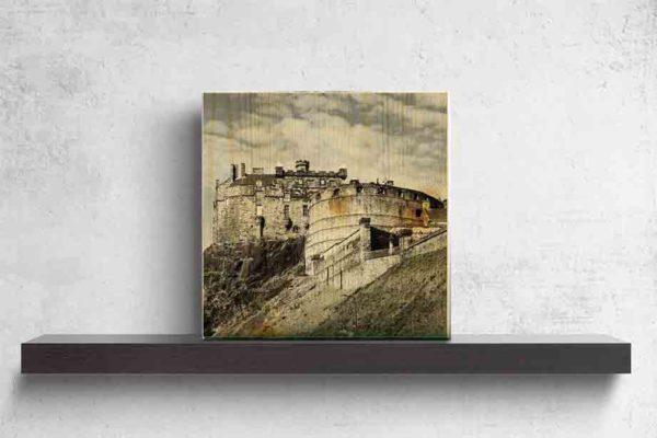 """Schottland Edinburgh. Es zeigt das Bild des Wahrzeichens der Stadt Edinburgh, die Höhenburg """"Edinburgh Castle"""", gelegen auf einem Felsen dem """"Castle Rock"""". Die Burg ist aus grauem Naturstein und es sind 2 Gebäude der Burg zu sehen. Ein Gebäude ist rund und das andere Gebäude ist eckig. Unter dem eckigen Gebäude ist der Felsen zu sehen auf dem die Burg gebaut ist. Außerdem ist eine Mauer zu sehen, hinter welcher sich der Vorhof zur Burg befindet. Das Holzbild ist im Querformat und steht auf einem schwarzen Wandregal vor weißem Hintergrund."""