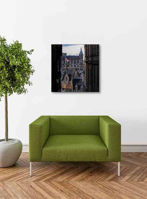 Schottland Edinburgh. Es zeigt das Bild durch 2 ältere Stadthäuser in Edinburgh, genannt Close, mit Blick auf den berühmten Bahnhof Waverley. Es sind verschiedene Hausdächer in historischem Stil und einen Fahnenmast mit der Flagge Großbritanniens zu sehen. Hinter den Hausdächern ist das historische und imposante Gebäude des Bahnhofs von Edinburgh. Das Alu Dibond Bild hängt an einer stylische eingerichteten Wohnzimmerwand.