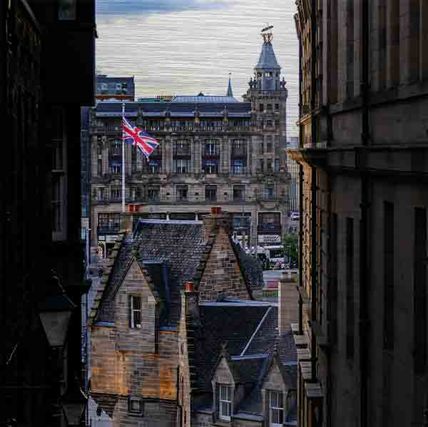 Schottland Edinburgh. Es zeigt das Bild durch 2 ältere Stadthäuser in Edinburgh, genannt Close, mit Blick auf den berühmten Bahnhof Waverley. Es sind verschiedene Hausdächer in historischem Stil und einen Fahnenmast mit der Flagge Großbritanniens zu sehen. Hinter den Hausdächern ist das historische und imposante Gebäude des Bahnhofs von Edinburgh. Das Bild ist quadratisch und in Farbe.