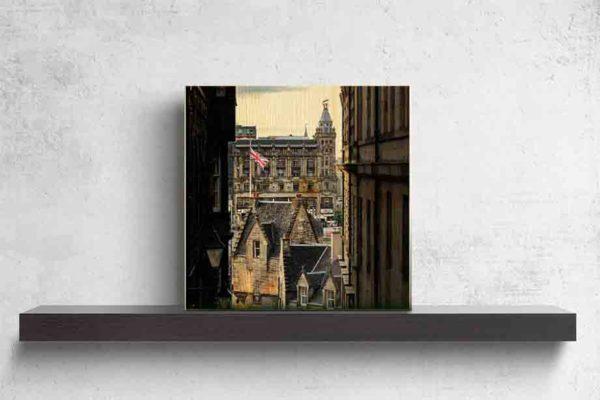 Schottland Edinburgh. Es zeigt das Bild durch 2 ältere Stadthäuser in Edinburgh, genannt Close, mit Blick auf den berühmten Bahnhof Waverley. Es sind verschiedene Hausdächer in historischem Stil und einen Fahnenmast mit der Flagge Großbritanniens zu sehen. Hinter den Hausdächern ist das historische und imposante Gebäude des Bahnhofs von Edinburgh. Das Holzbild ist im Querformat und steht auf einem schwarzen Wandregal vor weißem Hintergrund.
