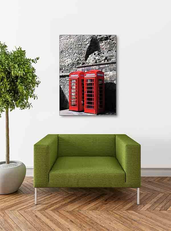 Schottland Edinburgh. Es zeigt das Bild von 2 britischen Telefonzellen, die nebeneinander vor einer grauen Natursteinwand, welche charakteristisch für Edinburgh ist, stehen. Die Telefonzellen sind in knalligem Rot. Das Bild ist im Hochformat und in Farbe. Das Alu Dibond Bild hängt an einer stylische eingerichteten Wohnzimmerwand.