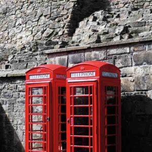 Schottland Edinburgh. Es zeigt das Bild von 2 britischen Telefonzellen, die nebeneinander vor einer grauen Natursteinwand, welche charakteristisch für Edinburgh ist, stehen. Die Telefonzellen sind in knalligem Rot. Das Bild ist im Hochformat und in Farbe.